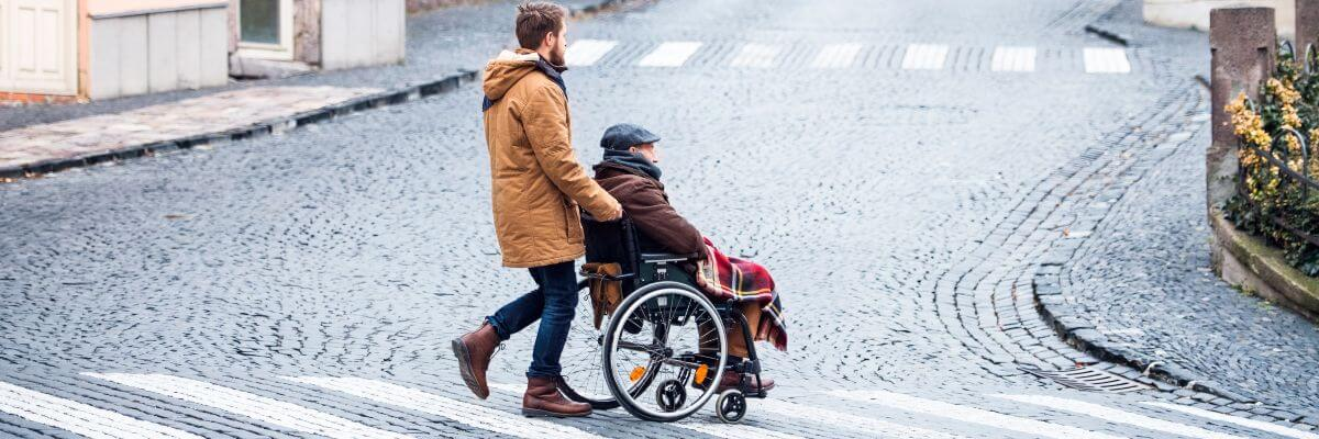 Young man pushing older man in wheelchair