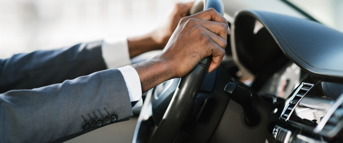 close up of man with hands on steering wheel