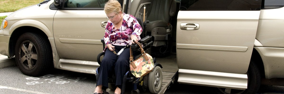 woman in wheelchair exiting her car via a built-in ramp