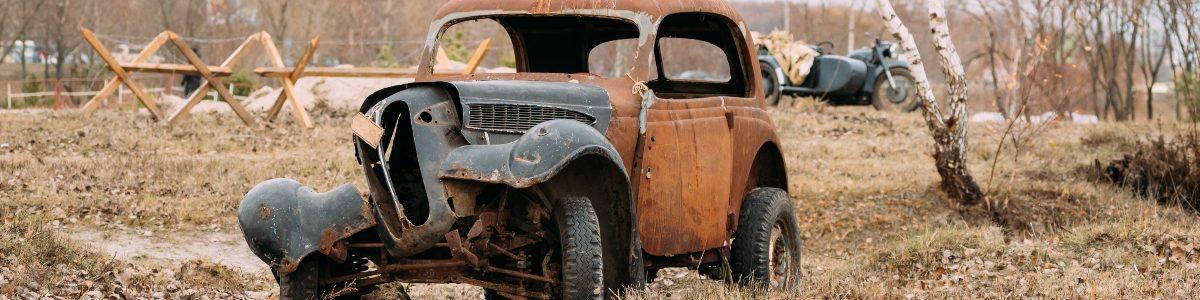broken down rusty car in field