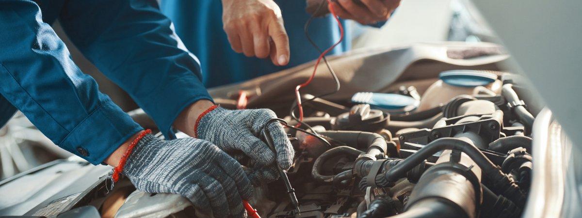 mechanics testing a car battery