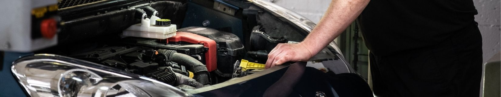 mechanic servicing a car with the bonnet lifted on the car