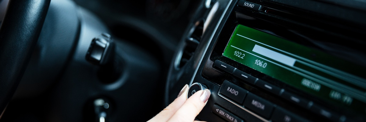Women adjusting volume of car stereo